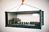 Abstract conference room interior inside cargo container suspended on crane hook on light background. 3D Rendering