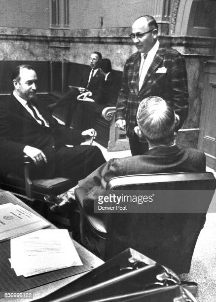 Conferring in Senate chamber before the address by Gov John Love are Sen Ray Braider seated right RLaJara Sen Bill Bledsoe left rHugo and Rep Robert...