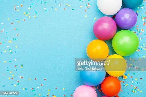 Confeti y globos de colores para cumpleaños fiesta en vista azul mesa. Estilo completamente laico. : Foto de stock
