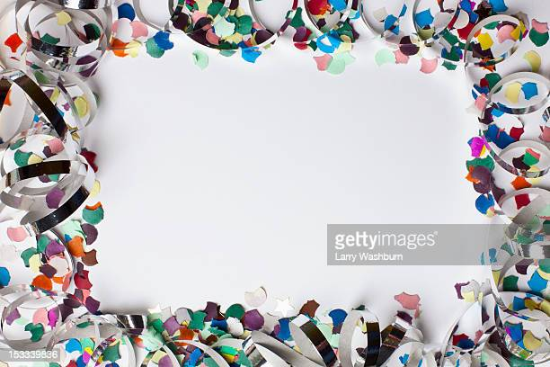 Confetti and streamers arranged into a square shaped frame