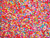 Confetti diversity background. Texture colored circles from paper, close-up. Basis for a festive design or a postcard. Carnival, abstract wedding or birthday backdrop