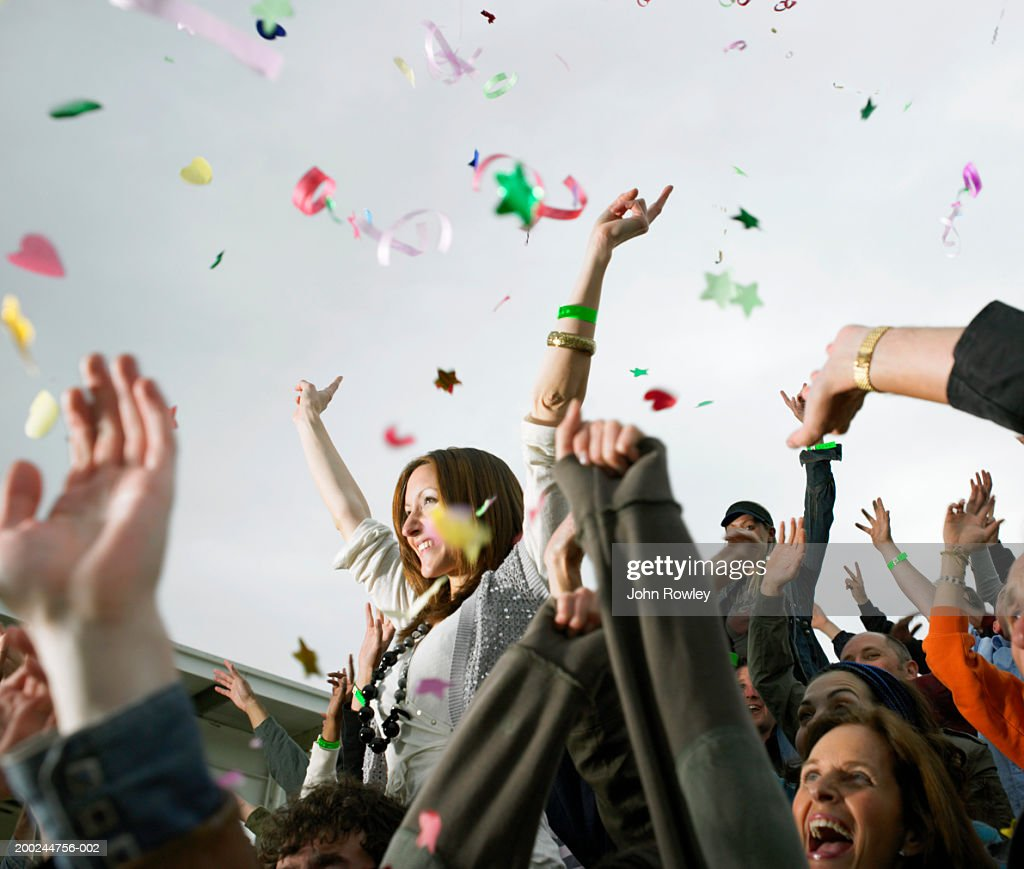 Confetti falling over crowd, woman on man's shoulders, cheering : Stock-Foto