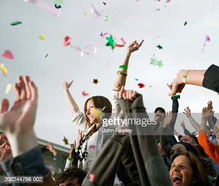Confetti falling over crowd, woman on man's shoulders, cheering : Stock Photo