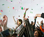 Confetti falling over crowd, woman on man's shoulders, cheering