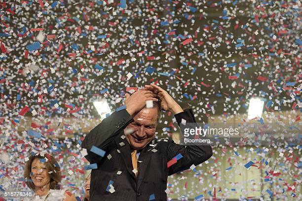Confetti falls on the head of John Kasich governor of Ohio and 2016 Republican presidential candidate after speaking during a campaign event in Berea...