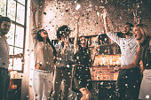 Group of happy young people throwing confetti and jumping while enjoying home party on the kitchen