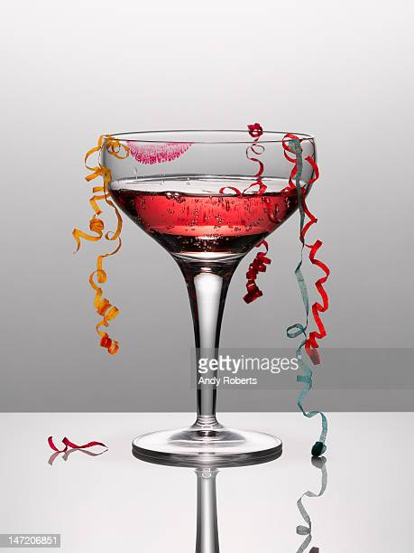 Confetti hanging from glass of pink champagne with lipstick stain