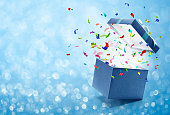 Confetti popping out from blue gift box - bokeh background