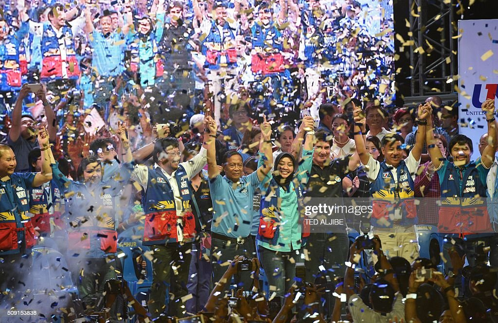 Confetti rains down as the head of the opposition party and presidential candidate Jejomar Binay (C) along with his senatorial line up led by boxing icon Manny Pacquiao (R) raise their hands during their proclamation rally in Manila on February 9, 2016. A cliffhanger race to lead the Philippines began February 9 with emotion-charged rallies by a dead movie star's adopted daughter, a politician who brags about killing criminals and other top contenders. AFP PHOTO / TED ALJIBE / AFP / TED ALJIBE