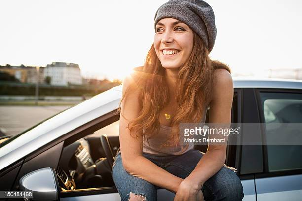Confidence woman sitting on car.