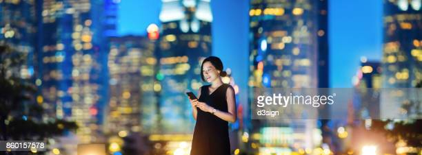 Confidence young woman using mobile phone with the night view of Hong Kong urban skyline