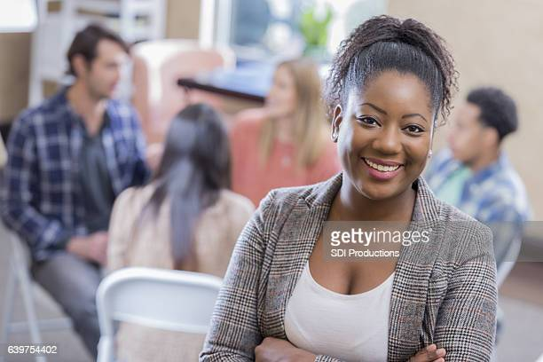 Confident African American counselor in front of support group