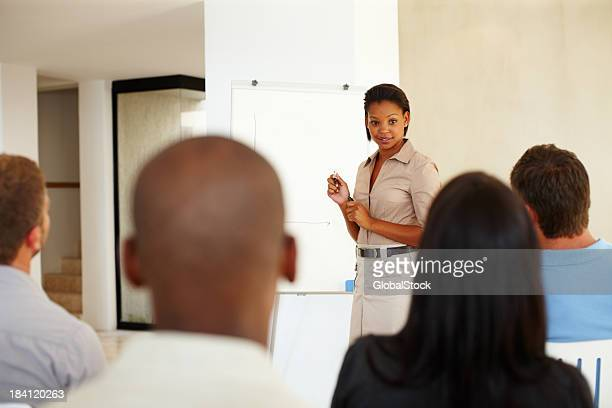 Confident African American executive giving presentation to colleagues