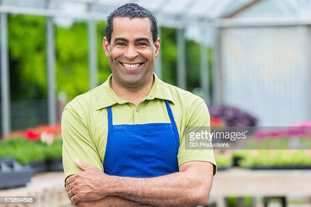 Confident African American garden center owner in greenhouse