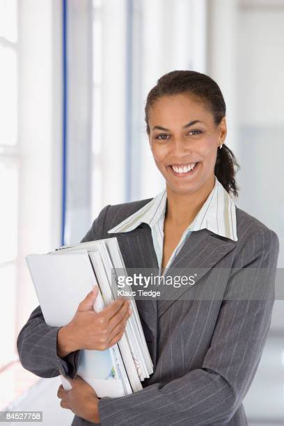 Confident African businesswoman holding paperwork