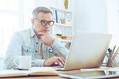 Thoughtful mature man looking at his laptop and keeping hand on chin while sitting at his working place