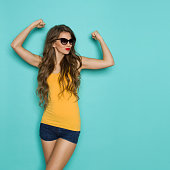 Beautiful young woman in jeans shorts and orange shirt posing with arms raised. Three quarter length studio shot on teal background.