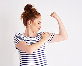 Confident and strong woman showing her bicep at studio shot