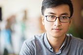 Portrait of confident Asian businessman in eyeglasses. Serious young manager looking at camera. Smart male student sitting alone. Young entrepreneur concept