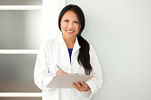 Confident Asian woman doctor taking notes on a clipboard when visiting a patient. This photo has been produced with professionals.