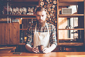 Young bearded man in apron looking at camera and holding coffee cup while standing at bar counter