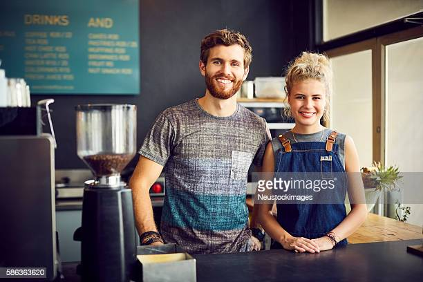 Confident baristas smiling together at counter