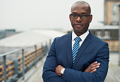 Confident black business man in a stylish suit standing with folded arms on a rooftop of n office block looking at the camera with a serious expression