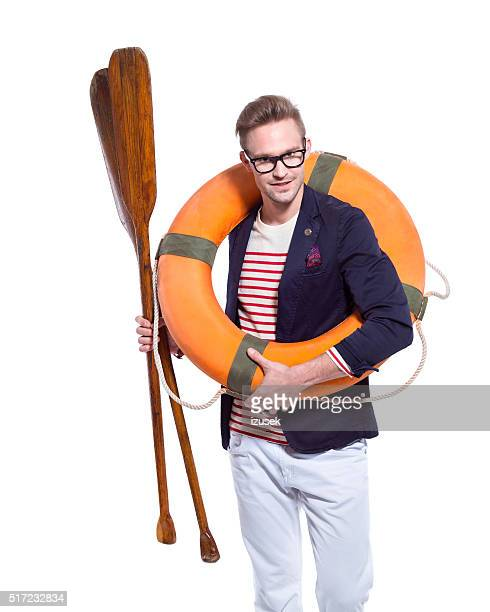 Confident blonde young man holding lifebuoy and paddle