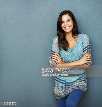 Confiante brunette inclina-se contra uma parede