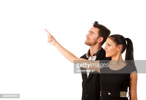 Confident business couple standing next to each other, pointing : Stock Photo