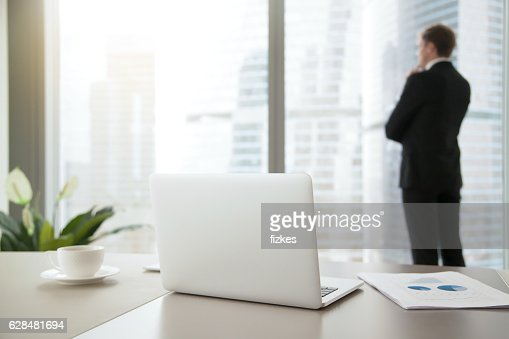 Confident business man contemplating in his office : Stock Photo