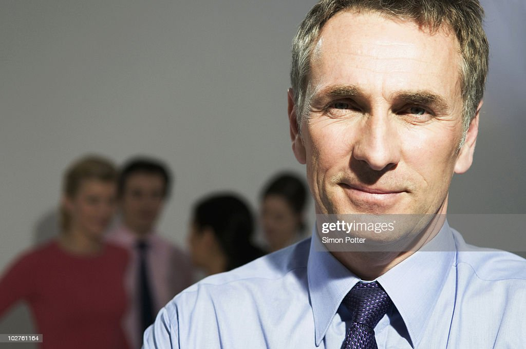 Confident business man looks to camera : Stock Photo