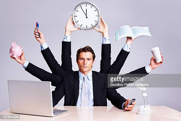 Confident business man multitasking at desk