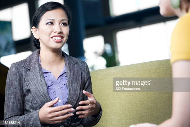 Confident Business Woman Explaining Something to Co-Worker