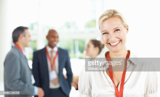 Confident business woman with colleagues in background