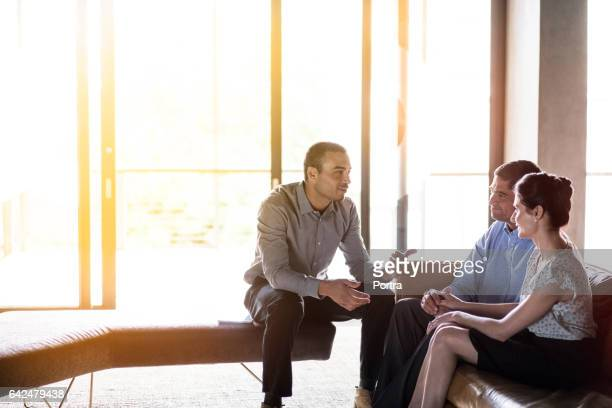 Confident businessman discussing with couple