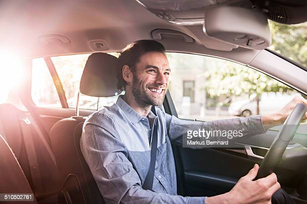 Confident businessman driving his car.