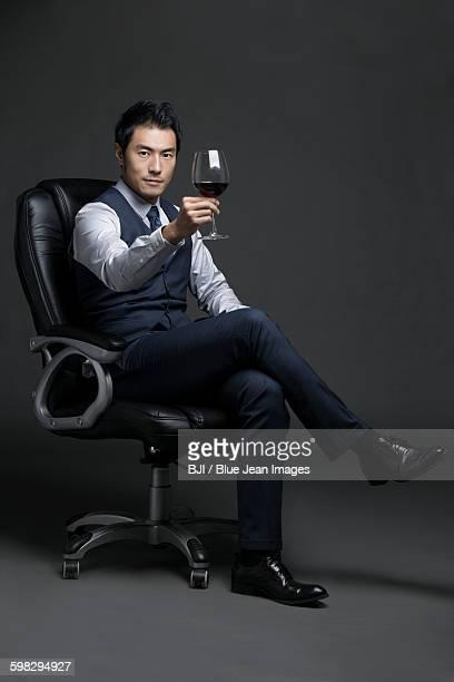 Confident businessman enjoying red wine
