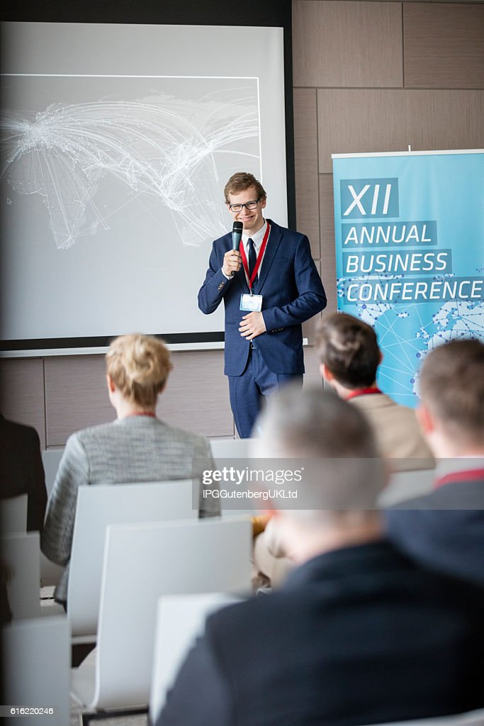 Confident businessman explaining strategy to audience in seminar hall : Stock Photo