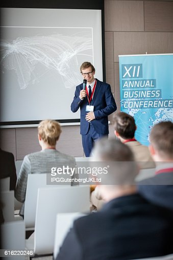 Confident businessman explaining strategy to audience in seminar hall : Photo