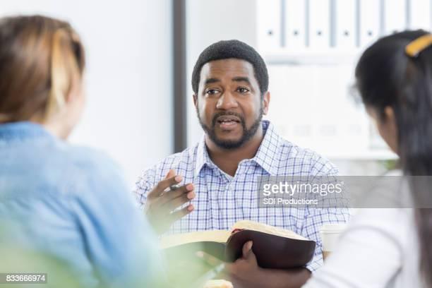 Confident businessman facilitates office Bible study
