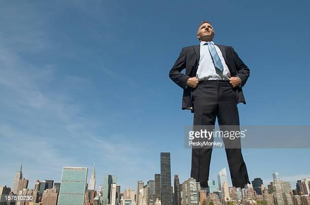 Uomo d'affari fiducioso che domina lo Skyline della città gigante
