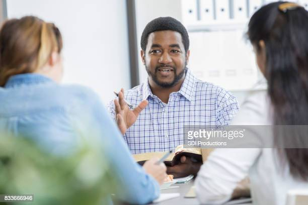 Confident businessman leads office Bible study during lunch