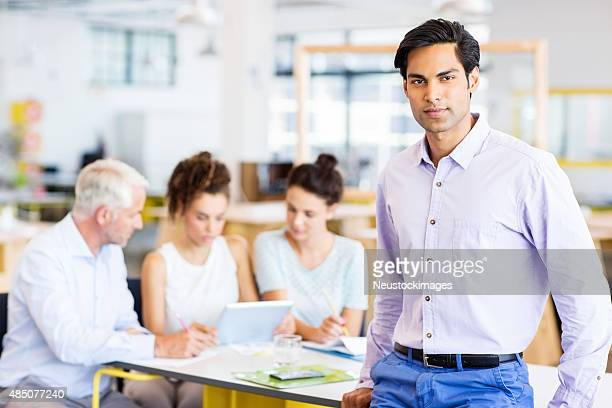 Confident Businessman Leaning On Conference Table