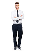 Full length of smiling young businessman keeping arms crossed and looking at camera while standing against white background