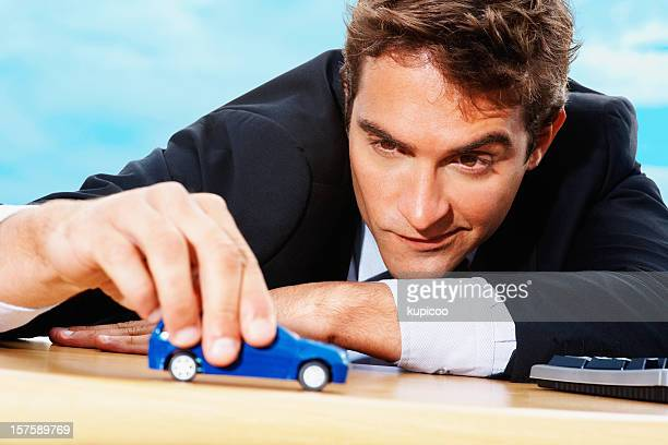 Confident businessman playing with a blue toy car