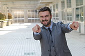 Confident businessman pointing at camera.