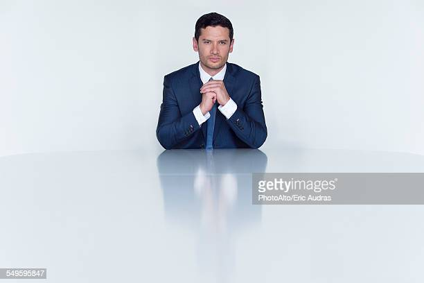 Confident businessman seated at table, portrait