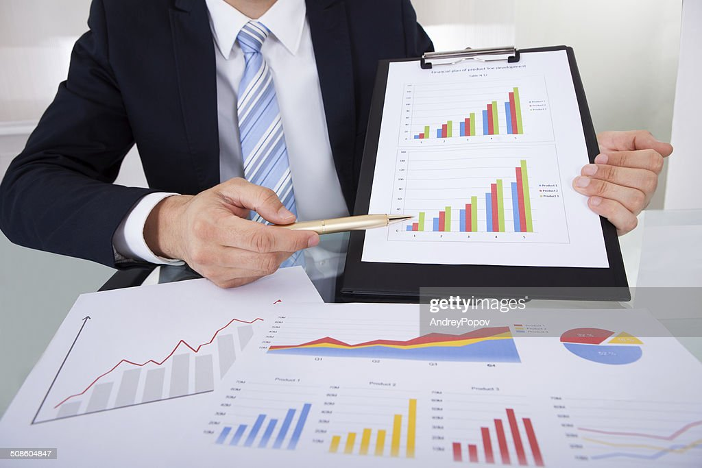 Confident Businessman Showing Graphs In Office : Stock Photo