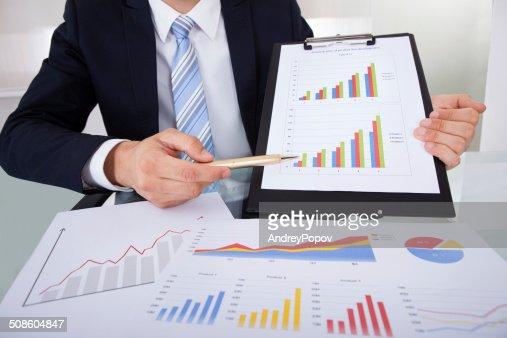 Seguro empresario mostrando gráficos en oficina : Foto de stock